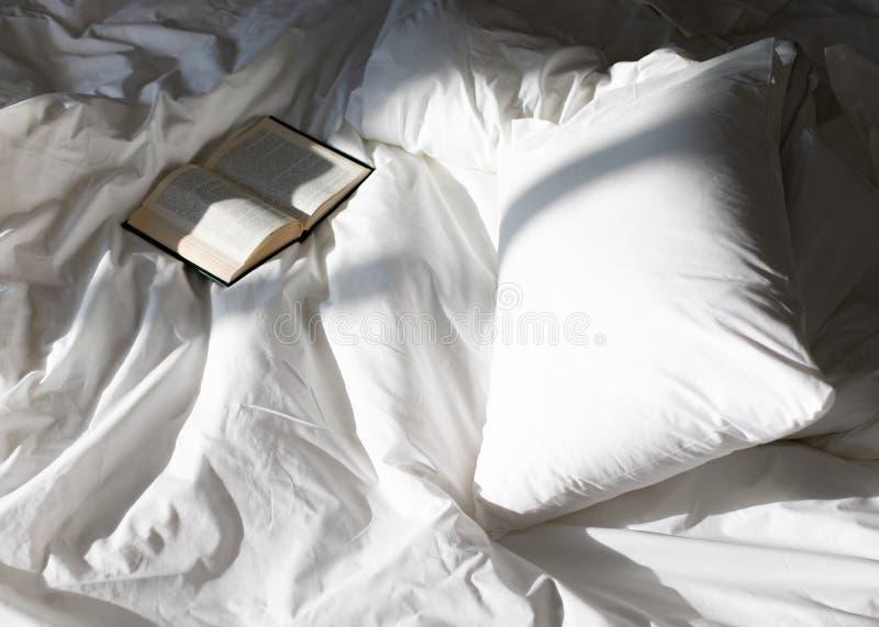 Composición creativa de la foto con el libro y cama blanca bajo luz del sol de la ventana imagen de archivo