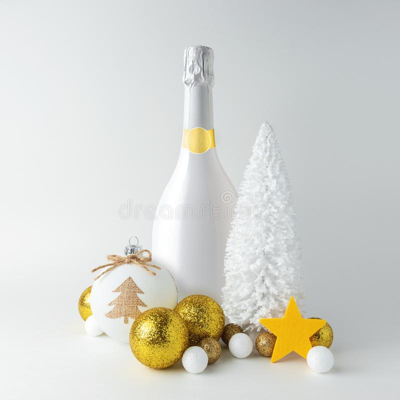 Composición creativa de Navidad con botella de champán blanco y decoración dorada de Navidad Concepto mínimo de Navidad o Año Nue fotografía de archivo libre de regalías