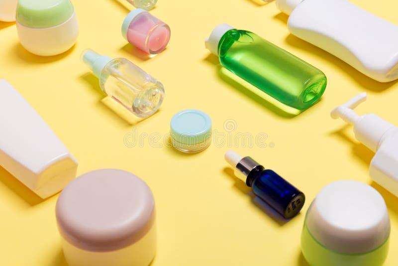 Composición de diversos tarros y botellas cosméticos clasificados en fondo amarillo Concepto del cuidado de la belleza con el esp imagen de archivo libre de regalías