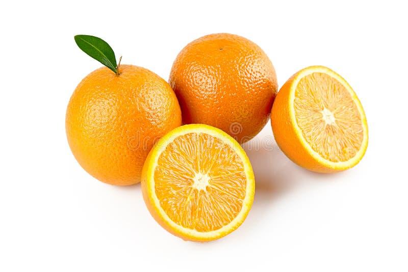 Composici?n de dos naranjas con la hoja y la media fruta anaranjada aisladas en el fondo blanco con la trayectoria de recortes Re imagen de archivo libre de regalías