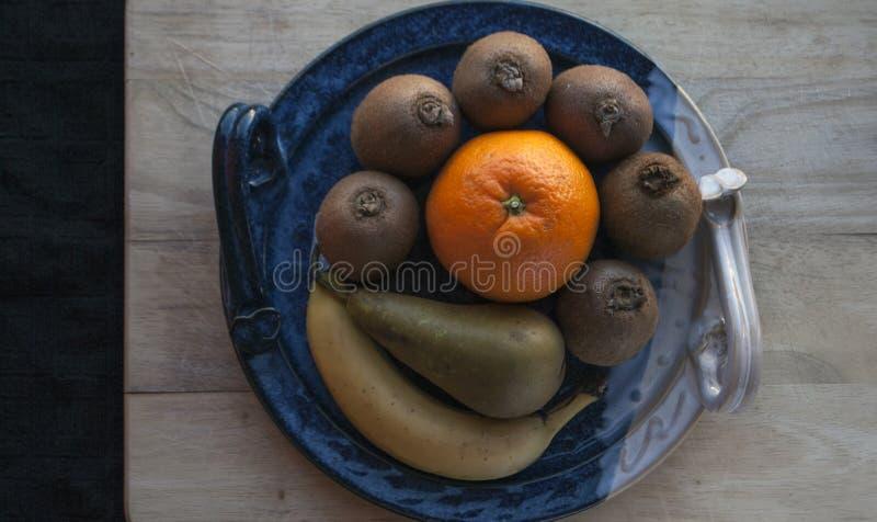 Composición de frutas en un disco azul decorativo en un tablero de madera con un paño negro en el fondo imagen de archivo libre de regalías