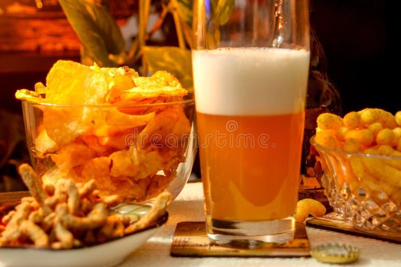 Composición de igualación hermosa con la cerveza y los bocados imagen de archivo libre de regalías
