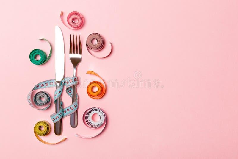Composición de la bifurcación y cuchillo rodeado con las cintas métricas balled coloreadas en fondo rosado Vista superior del con foto de archivo libre de regalías
