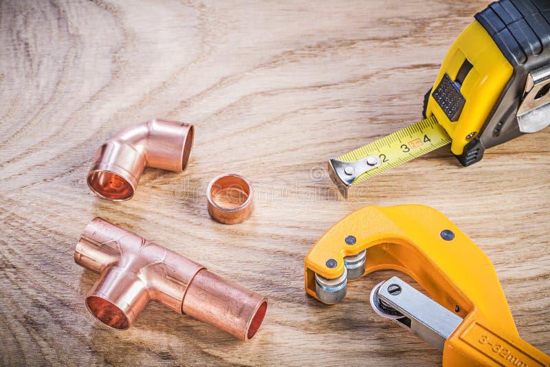 Composición de la cinta métrica de cobre amarillo de las colocaciones del cortador de tubo en la madera foto de archivo libre de regalías