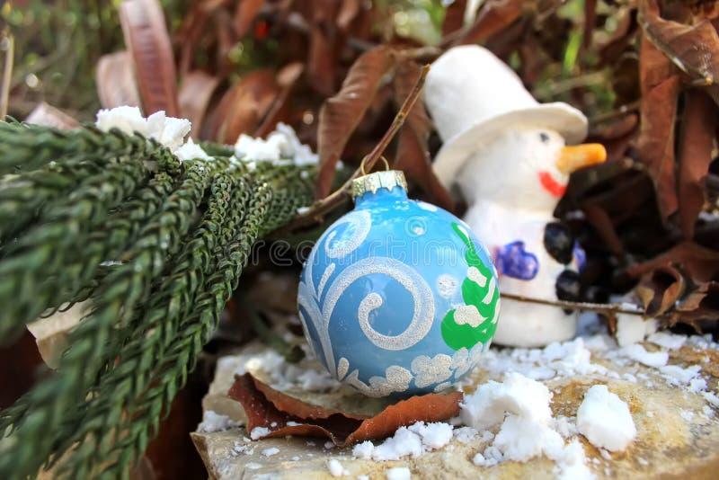 Composición de la Feliz Navidad o de la Feliz Año Nuevo, tarjeta de felicitación Bola y muñeco de nieve de la Navidad fotos de archivo libres de regalías