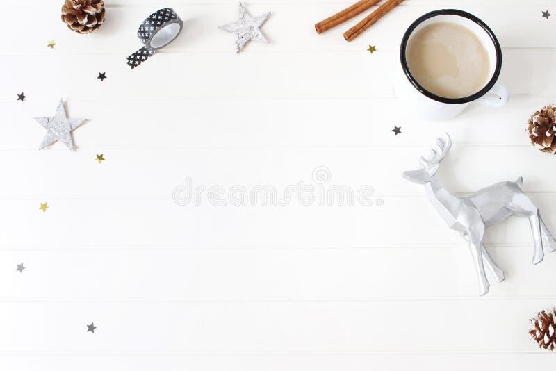 Composición de la Navidad Chocolate caliente, conos del pino, palillos de canela, confeti de las estrellas y reno en el fondo bla foto de archivo