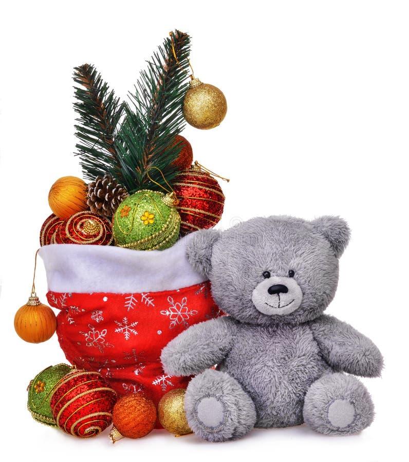 Composición de la Navidad con el bolso de Papá Noel por completo de juguetes y del oso de peluche sonriente fotografía de archivo