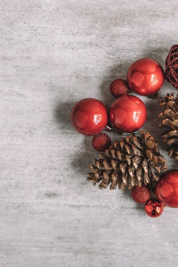 Composición de la Navidad con las chucherías y los conos rojos del pino en de madera foto de archivo