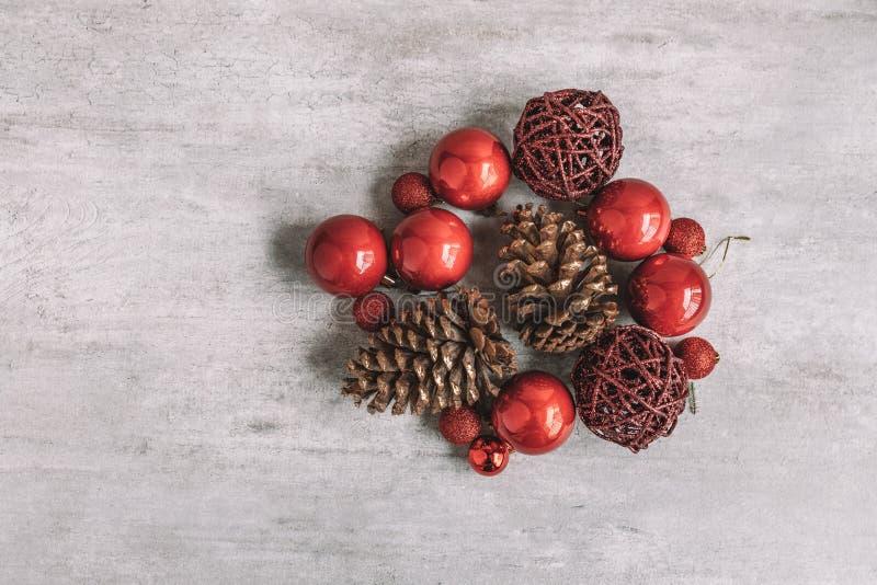 Composición de la Navidad con las chucherías y los conos rojos del pino en de madera fotografía de archivo
