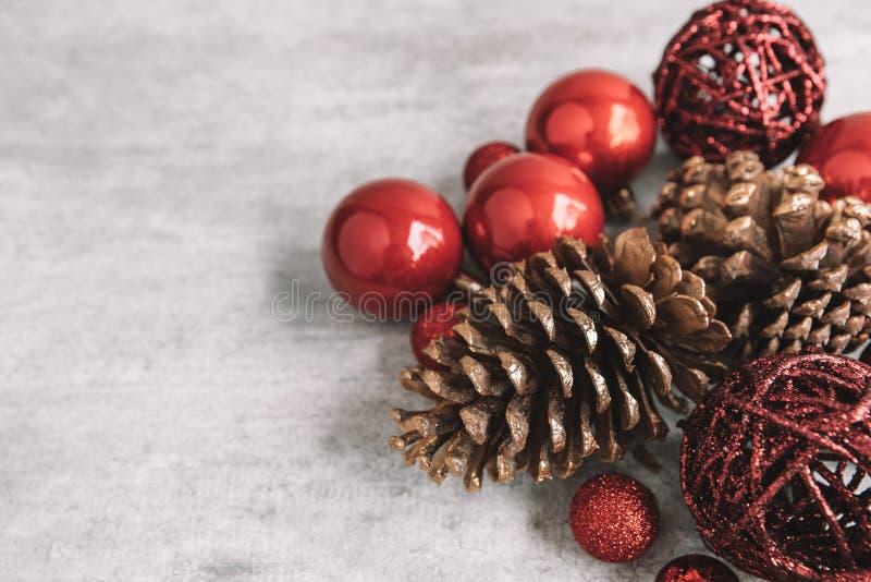 Composición de la Navidad con las chucherías y los conos rojos del pino en de madera imagenes de archivo