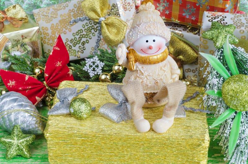Composición de la Navidad con las decoraciones Muñeco de nieve alegre que se sienta en un regalo imágenes de archivo libres de regalías