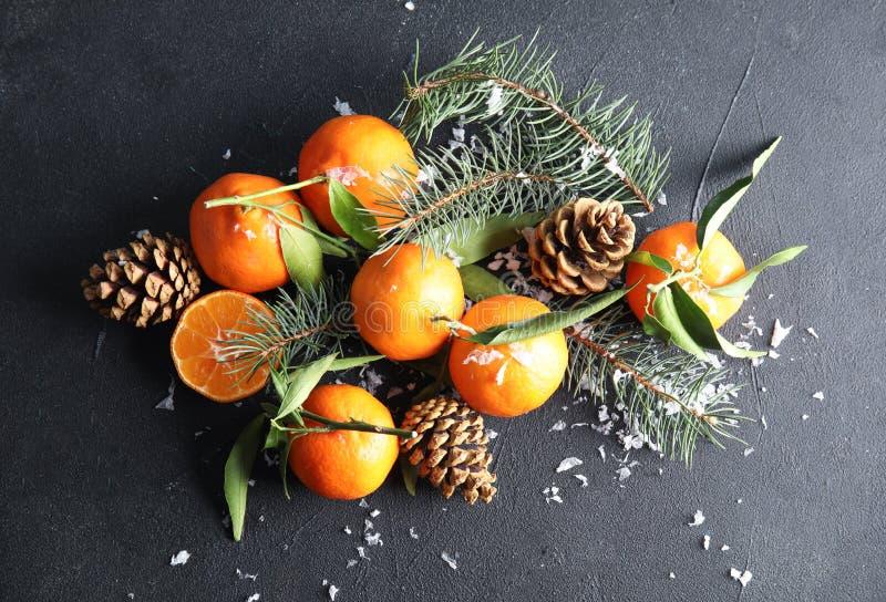 Composición de la Navidad con las mandarinas maduras en fondo negro fotografía de archivo