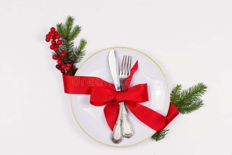 Composición de la Navidad con la placa, los cubiertos, las ramas del pino, la cinta y las bayas rojas en la tabla blanca Fondo de foto de archivo
