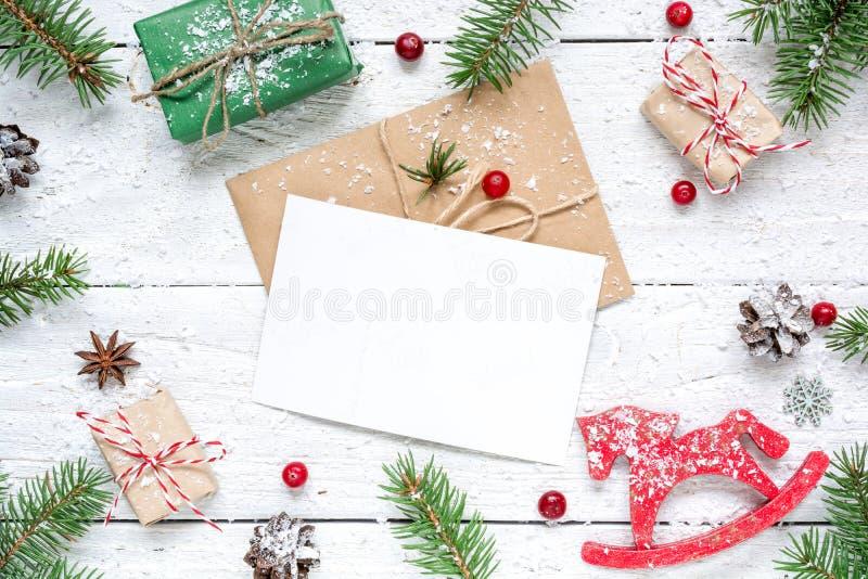 Composición de la Navidad con la tarjeta de felicitación en blanco ramas de árbol de abeto, juguete del caballo, cajas de regalo  imagenes de archivo