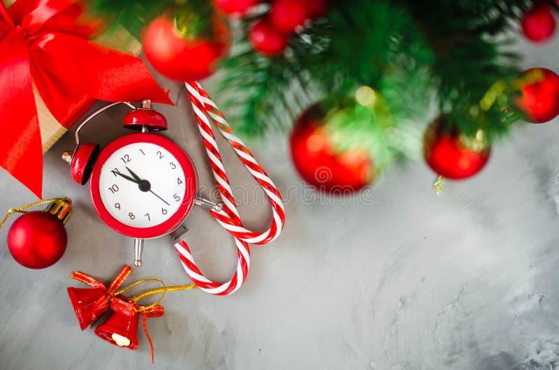 Composición de la Navidad: el abeto de Navidad ramifica, despertador, caja de regalo y las decoraciones foto de archivo