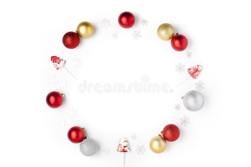 Composición de la Navidad Guirnalda hecha de copos de nieve, de rojo, de plata, de bolas del oro y de piruletas en el fondo blanc foto de archivo libre de regalías