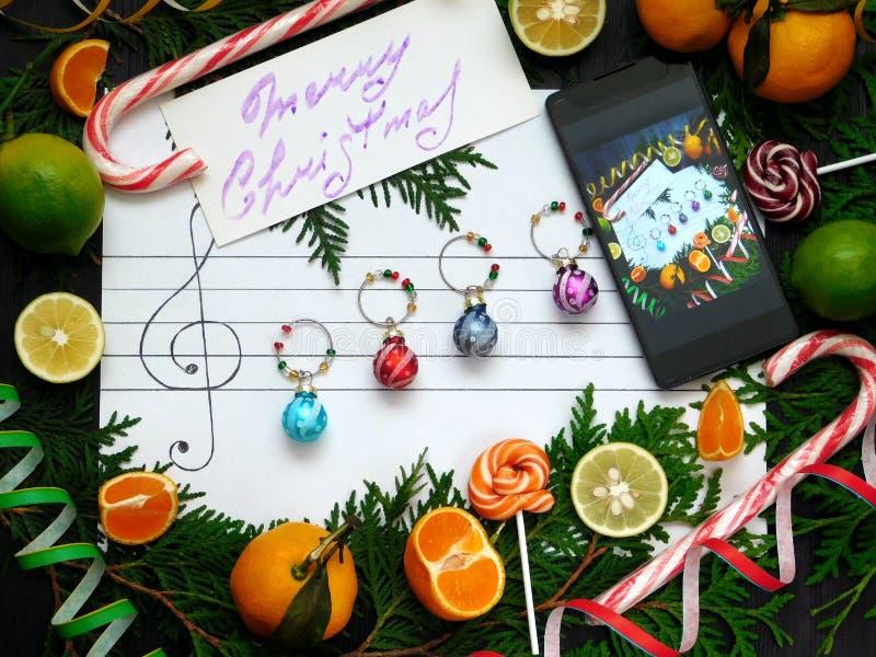Composición de la Navidad Las bolas de la decoración se arreglan en el papel como notas de la música Concepto de la melodía de la imágenes de archivo libres de regalías