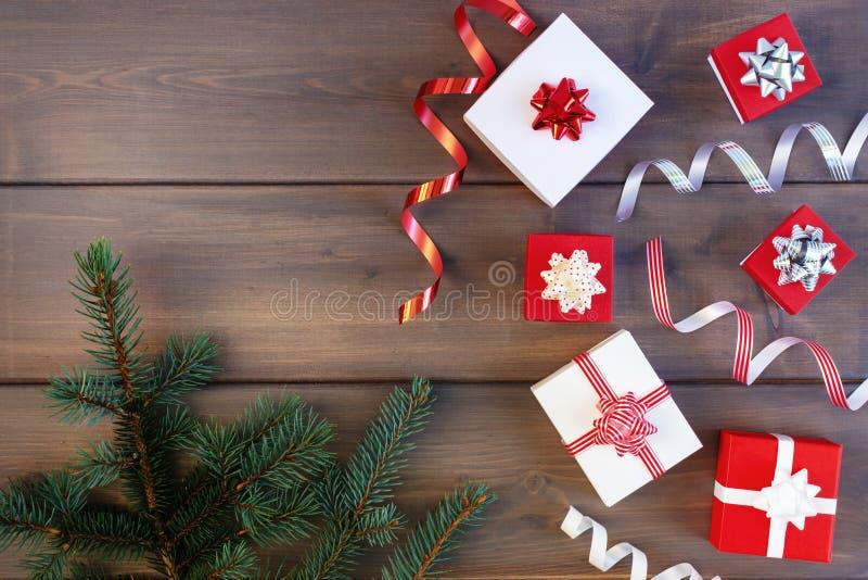Composición de la Navidad de las cajas de regalo rojas y blancas, de las cintas decorativas y de las ramas de un árbol de navidad foto de archivo
