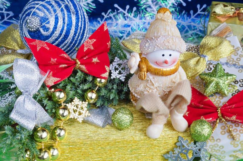 Composición de la Navidad Muñeco de nieve alegre en el regalo y decoraciones imagen de archivo