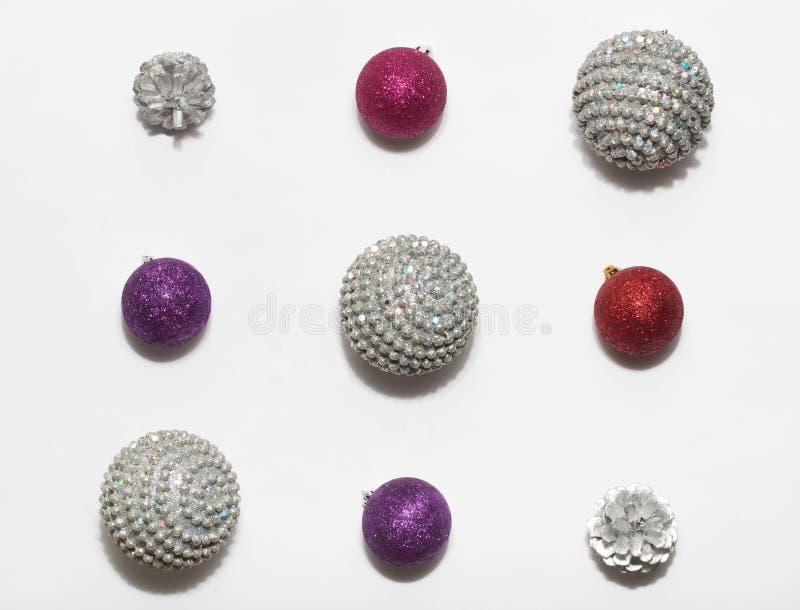 Composición de la Navidad Plata de la Navidad, rojo, bola púrpura y conos del pino de plata, en el fondo blanco fotografía de archivo