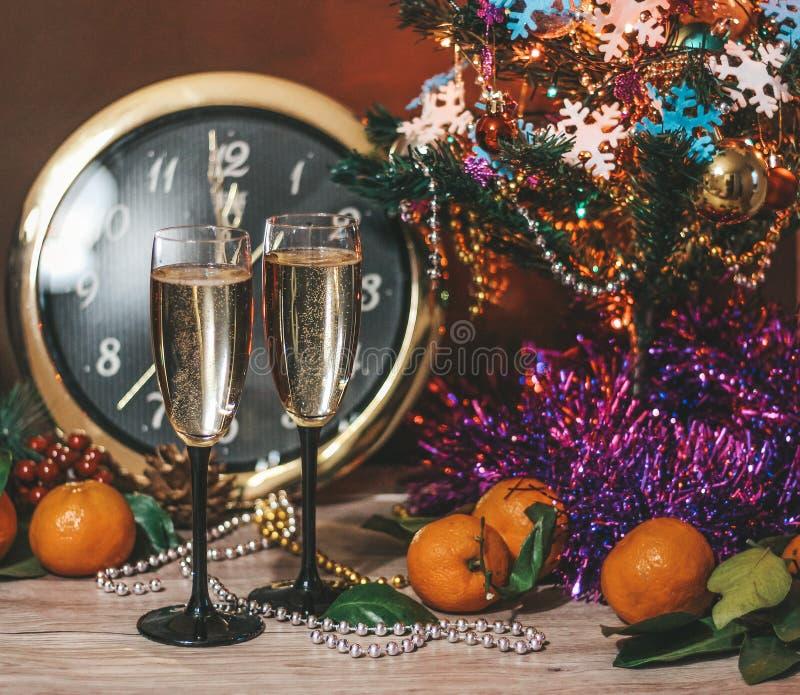Composición de la Navidad que consiste en los relojes, vidrios de champán con las burbujas, árbol de navidad adornado, mandarinas imagen de archivo