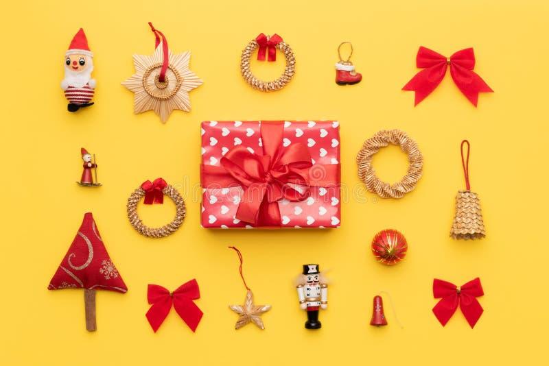 Composición de la Navidad Regalo rojo de la Navidad y muchos ornamentos retros de la Navidad aislados en fondo amarillo brillante foto de archivo