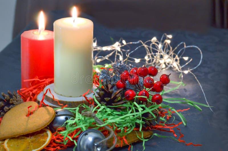 Composición de la Navidad: velas ardientes rojas y blancas en una tabla festiva en un fondo oscuro Pan de jengibre, malla, adorno fotos de archivo