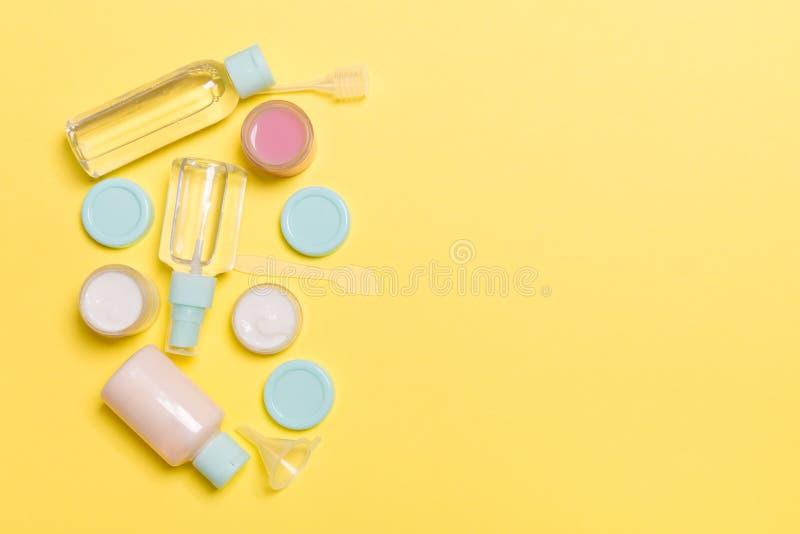 Composición de la visión superior de pequeños botellas y tarros que viajan para los productos cosméticos en fondo amarillo Concep fotografía de archivo