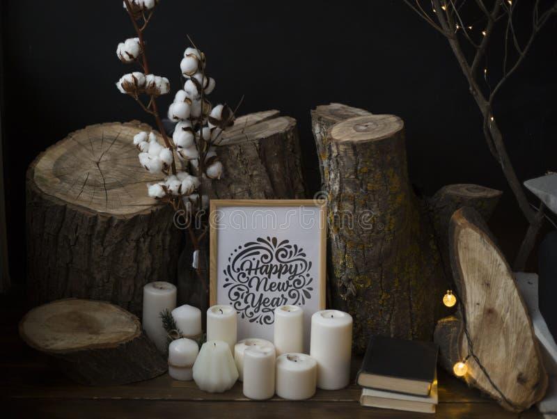 Composición de las talas de árboles contra un fondo oscuro, colocándose en un piso de madera así como velas y una inscripción fotos de archivo