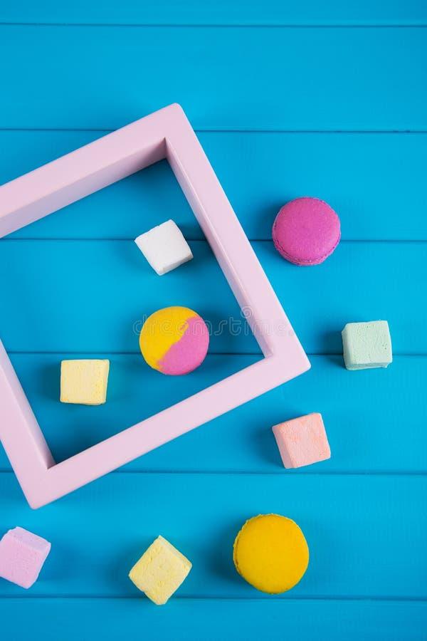 Composición de los alimentos de Minimalistic de macarrones coloridos y de la melcocha cuadrada con el marco rosado en fondo azul  fotografía de archivo