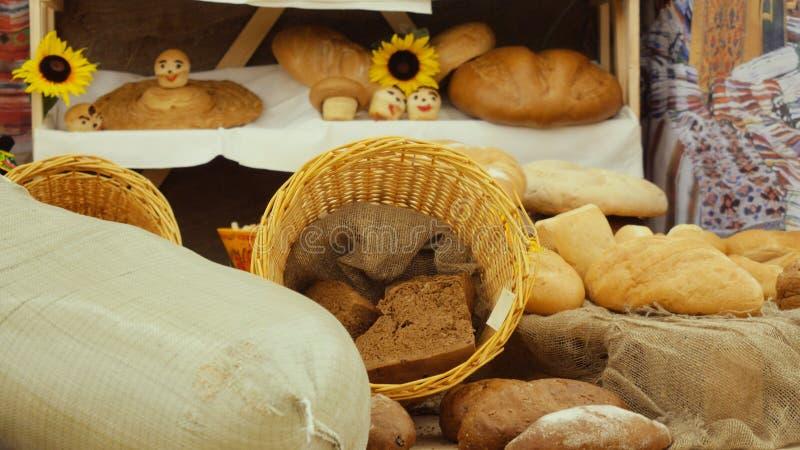 Composición de los panes de centeno, de la harina del bolso, de la cesta de mimbre y de baguettes con los girasoles en la tabla d foto de archivo libre de regalías