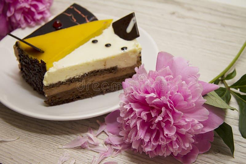 Composición de los pasteles de queso con las flores rosadas de la peonía fotografía de archivo libre de regalías