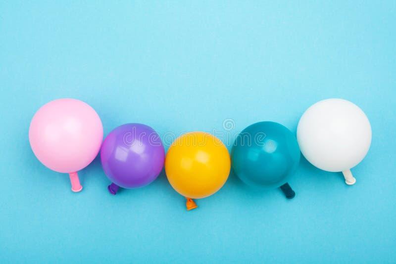 Composición de Minimalistic con los globos coloridos en la opinión de sobremesa azul Fondo del cumpleaños o del partido estilo pl foto de archivo libre de regalías