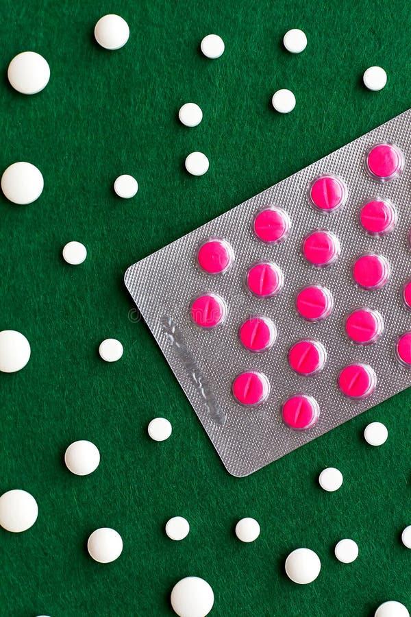 Composición de píldoras rosadas en la ampolla de plata y el pi blanco derramado imagenes de archivo