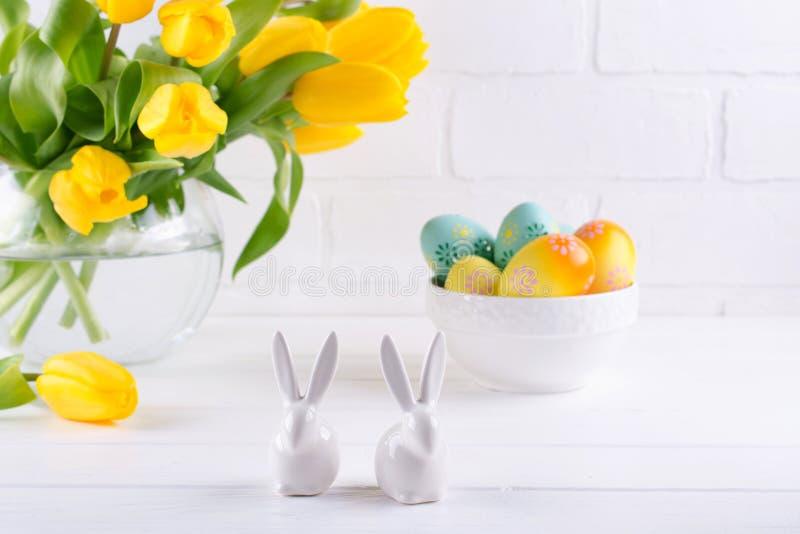 Composición de Pascua con el ramo de flores amarillas del tulipán en el florero de cristal y dos conejos de cerámica blancos en b imagen de archivo libre de regalías