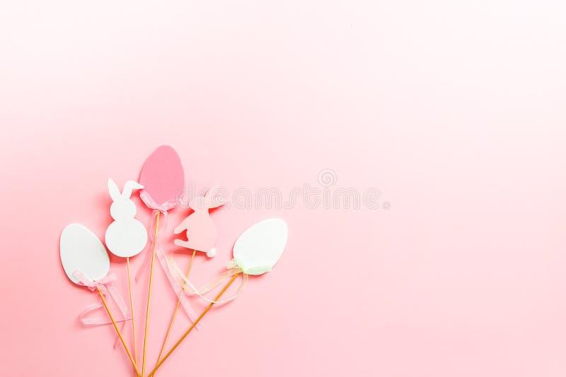 Composición de Pascua con la decoración tradicional Huevos y conejos decorativos en los palillos de madera en fondo suave rosado fotografía de archivo