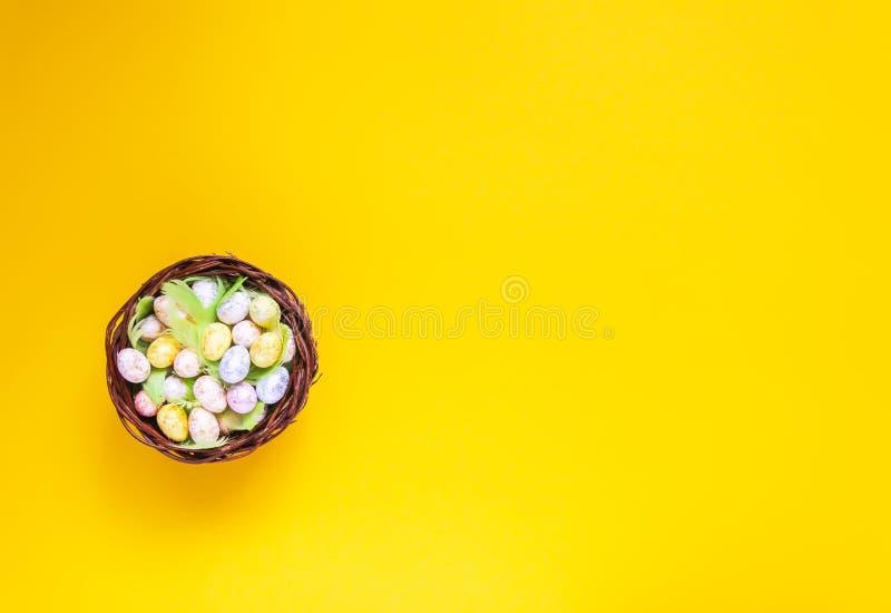 Composición de Pascua con la decoración tradicional Pequeños huevos y plumas coloridos en cesta de mimbre en fondo suave foto de archivo libre de regalías