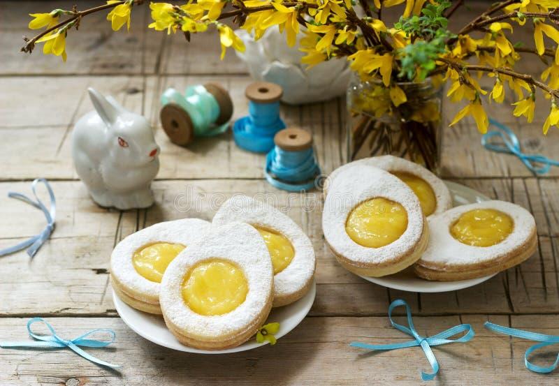 Composición de Pascua con las galletas oviformes llenadas de la cuajada de limón, del conejo, del ramo de forsythia y de los arco foto de archivo libre de regalías