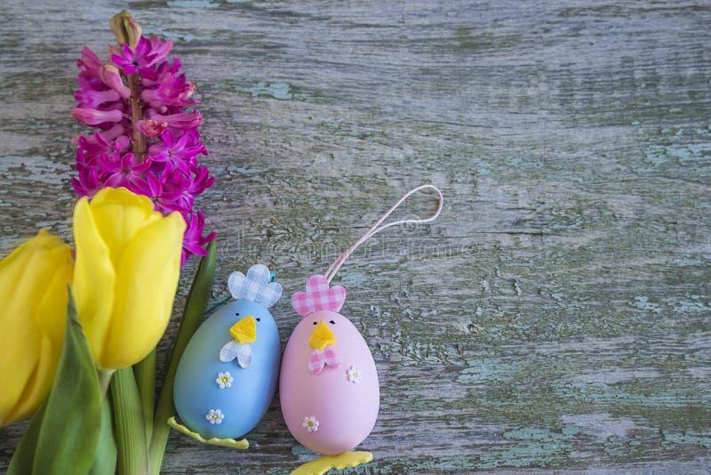 Composición de Pascua con los huevos adornados y las flores brillantes de la primavera foto de archivo