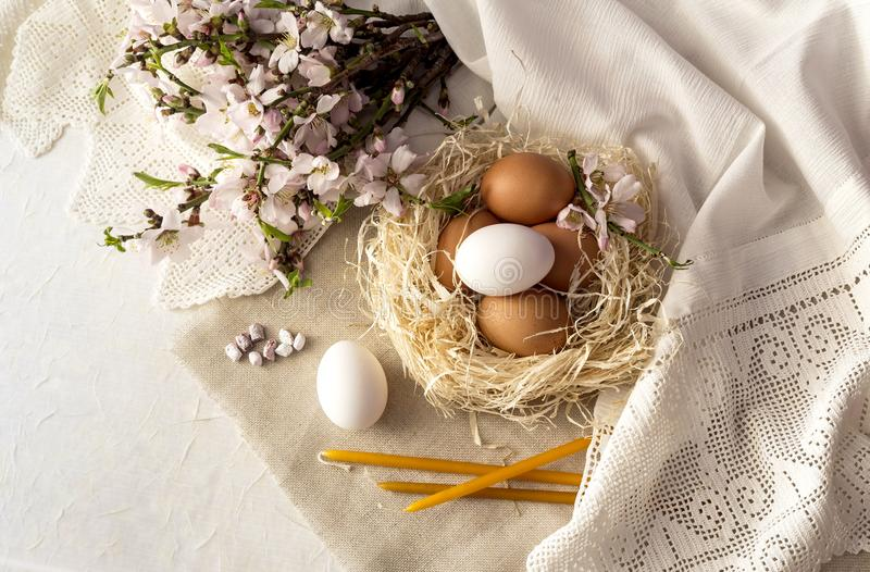 Composición de Pascua con los huevos en una jerarquía, velas de la iglesia, incienso y ramas de almendras florecientes foto de archivo