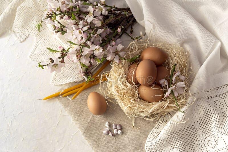 Composición de Pascua con los huevos en una jerarquía, velas de la iglesia, incienso y ramas de almendras florecientes fotografía de archivo