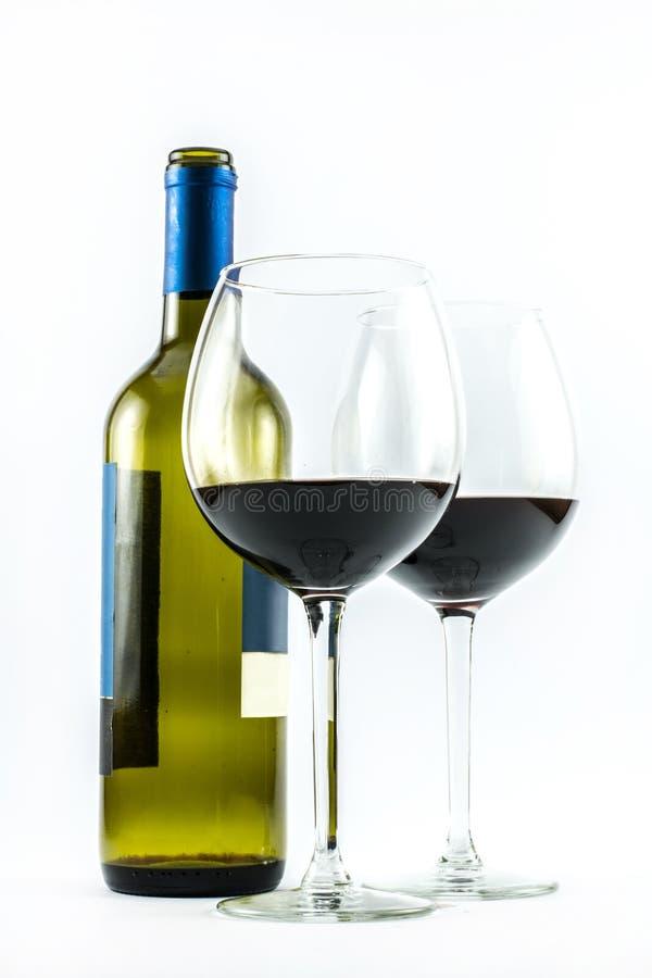 Composición de una botella exquisita de vino y de dos vidrios elegantes de vino rojo en un fondo blanco fotos de archivo