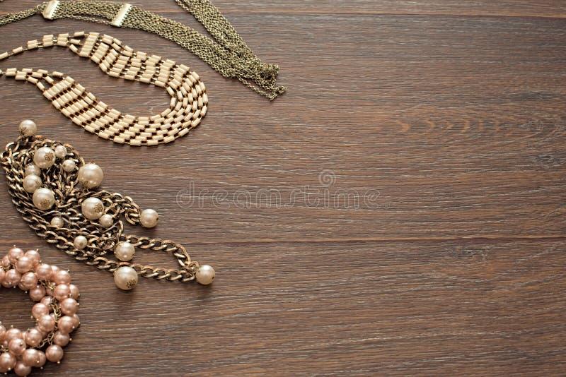 Composición decorativa de la joyería del ` s de las mujeres en fondo oscuro de madera foto de archivo libre de regalías
