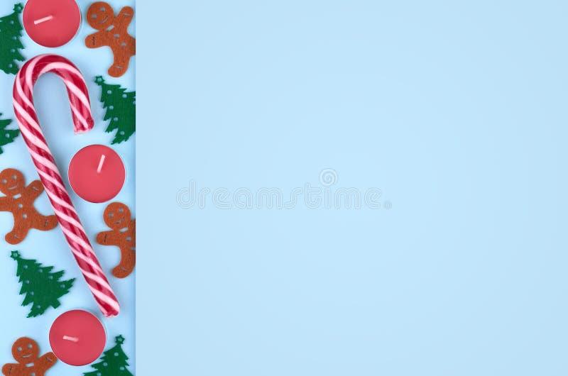 Composición del Año Nuevo con el caramelo, el árbol de pino, la vela y el hombre de pan de jengibre rayados Fondo del concepto de foto de archivo libre de regalías