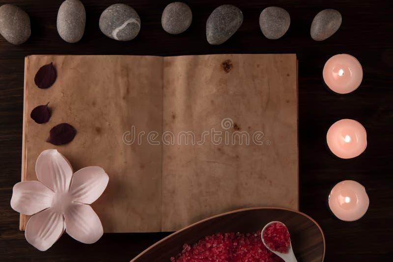 Composición del balneario con las velas del aroma y libro abierto del vintage vacío en fondo de madera Tratamiento, aromatherapy imágenes de archivo libres de regalías
