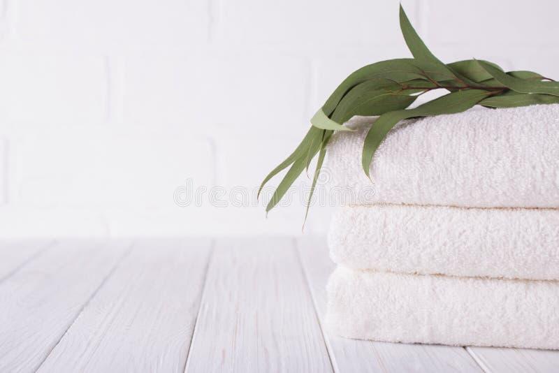 Composición del balneario en la tabla de madera Pila de tres toallas de baño mullidas blancas con la rama del eucalipto imagen de archivo