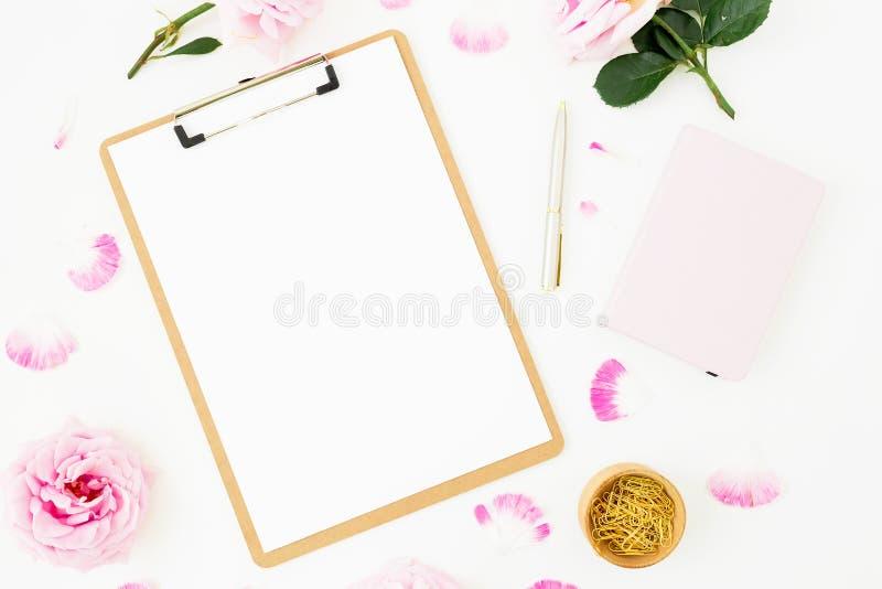 Composición del blog de la belleza con la lechería, el ramo rosado de las rosas y el tablero en el fondo blanco Visión superior E foto de archivo libre de regalías