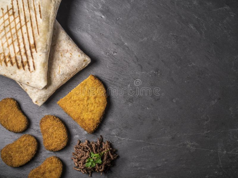Composición del bocado con los tacos franceses, cordon bleu, las pepitas y la carne de vaca en pizarra fotos de archivo