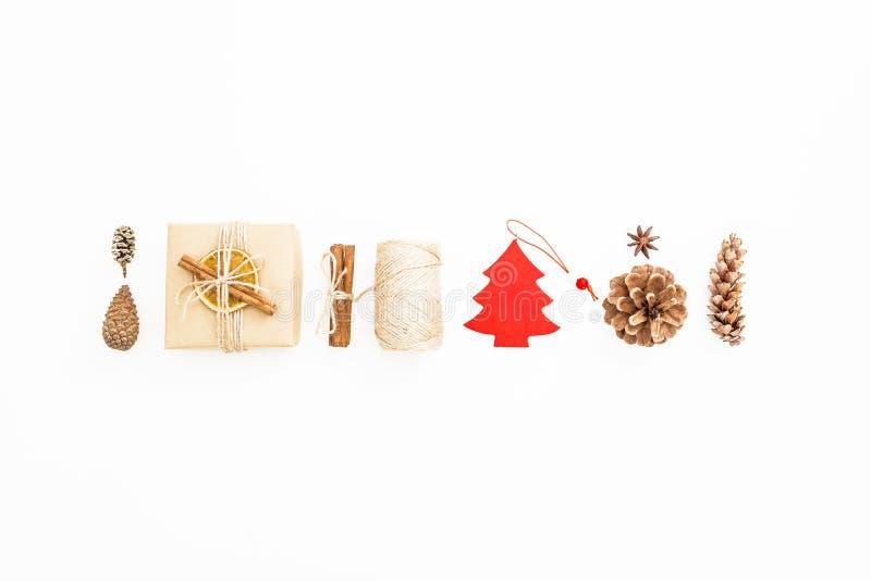 Composición del día de fiesta Caja de regalo, conos de la decoración de la Navidad, del canela y del pino en blanco Endecha plana ilustración del vector