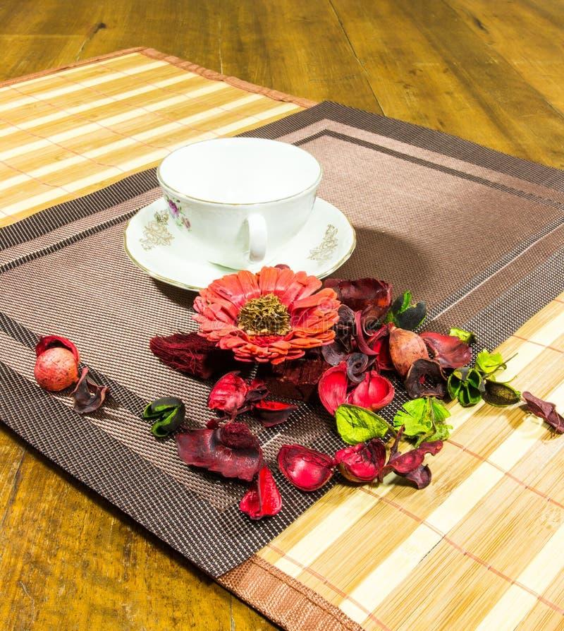 Composición del hogar rojo, verde que adorna las flores y hojas y una taza y una placa blancas en una tabla imagen de archivo libre de regalías